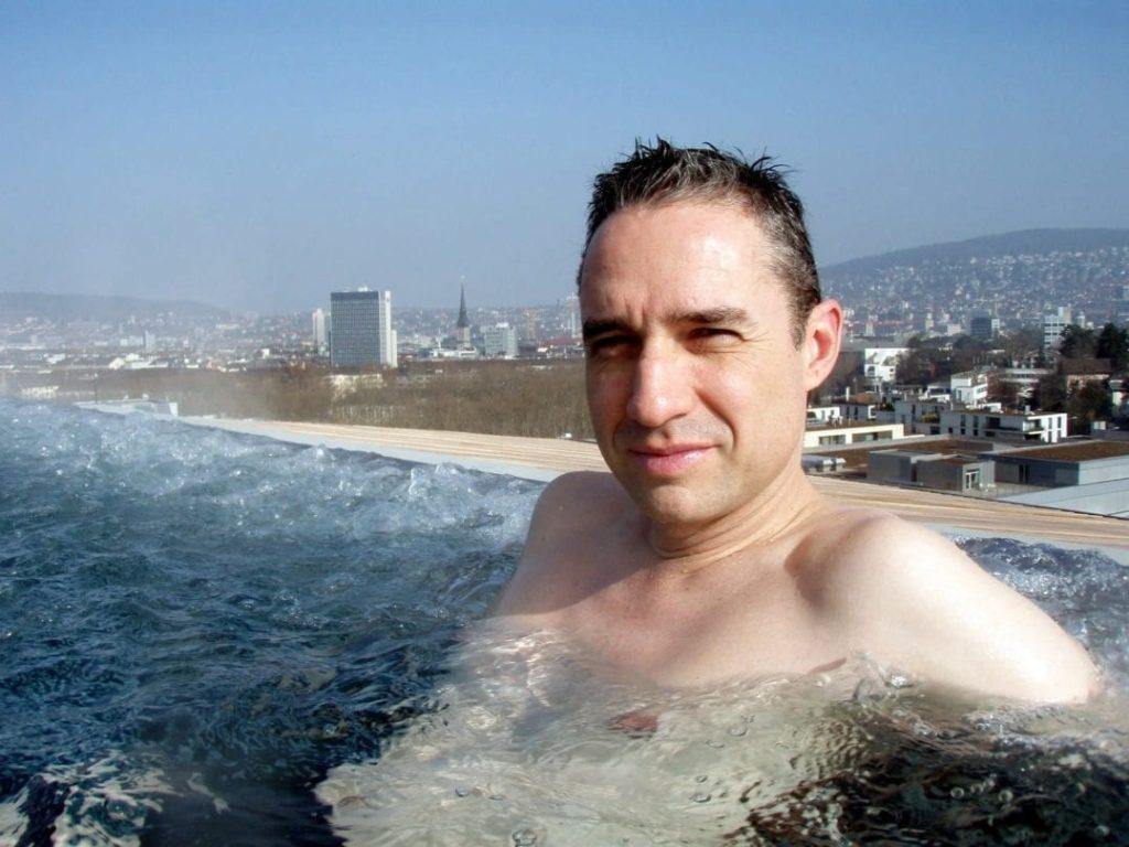 Walter Schärer auf dem Dachpool des Thermalbad & Spa Hürlimann mit Aussicht auf Zürich