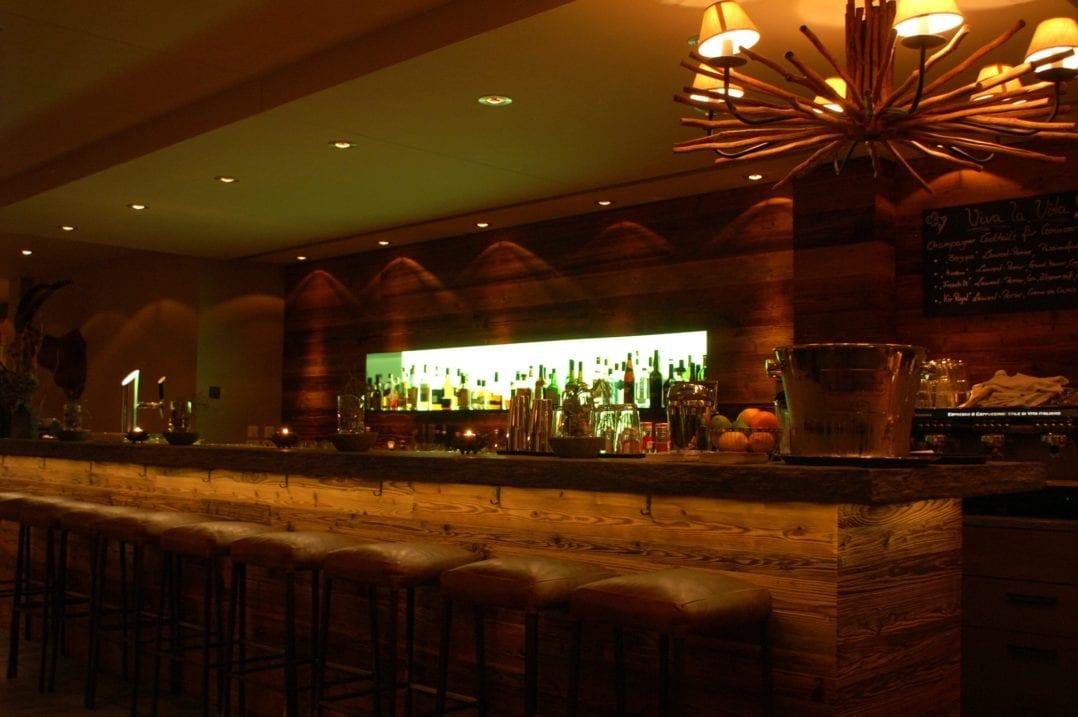 """Bar und Barhocker mit beleuchteten Flaschen im """"Da Rubi"""" im LA VAL Hotel in Brigels"""