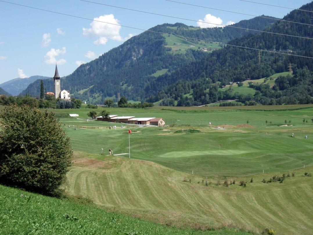 Kirche und Green des Buna Vista Golfplatzes in Sagogn, Graubünden