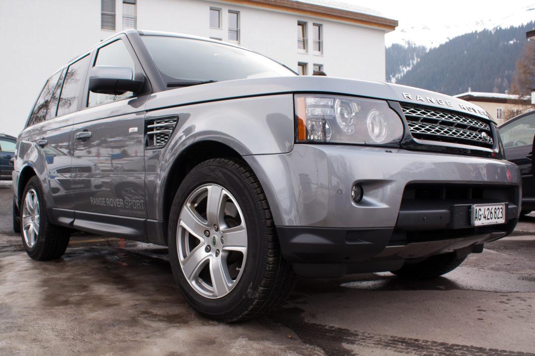 Kleine Eisfläche und Range Rover Sport auf dem Parkplatz des Jakobshorns, Davos