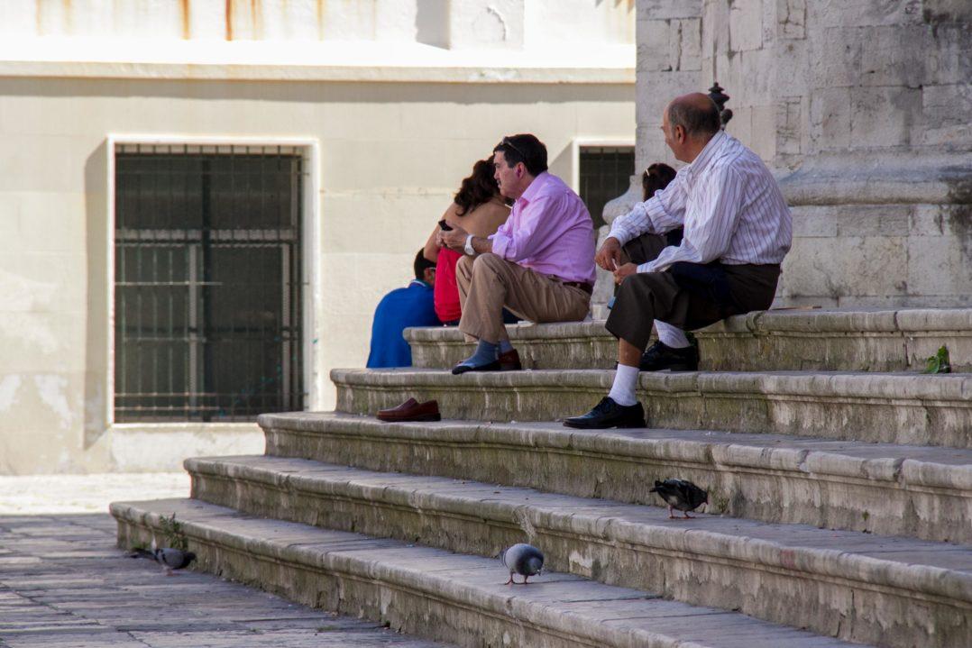Männer sonntags auf der Treppe der Kathedrale in Cádiz