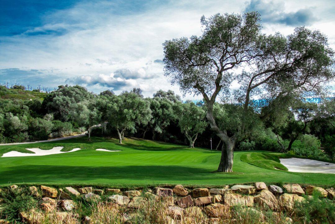 Grün 13 mit Golffahne, Bäumen und Bunkern im Finca Cortesin Golfplatz