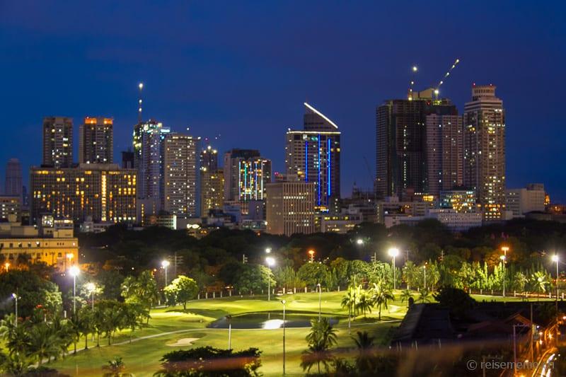Golfplatz in Manilas Stadtgraben vor Skyline