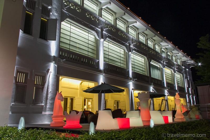 Beleuchtete Fassade und Schachfiguren des Mövenpick Heritage Hotels