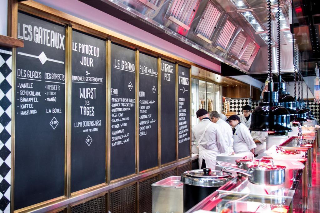 Menu und Köche hinter der offenen Showküche