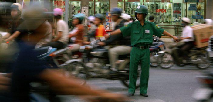 Junger Verkehrspolizist im dichten Verkehr von Saigon