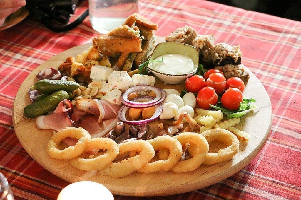 traditionelle litauische Vorspeisen: Zwiebelringe, Speck, Käse, Griebenschmalz- und Knoblauchbrot