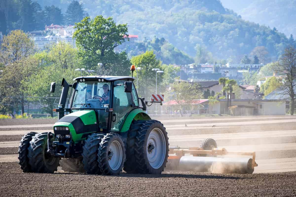 Traktor mit Reiswalze auf Reisfeld