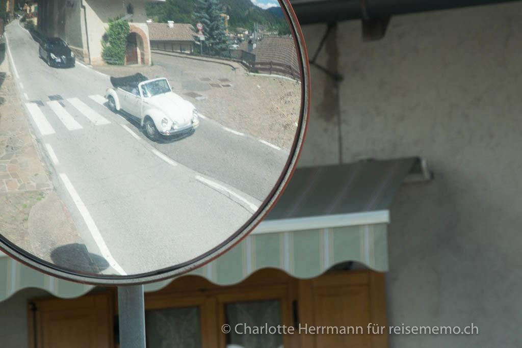 VW Käfer im Spiegel einer Ausfahrt