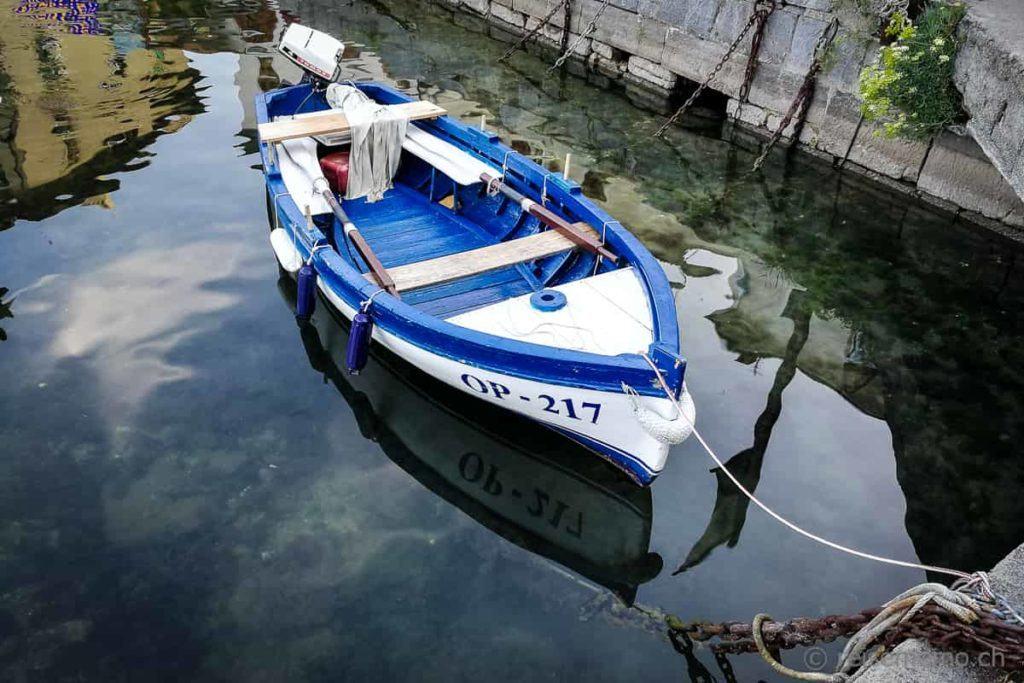 Vertäutes Fischerboot in seiner Reflektion