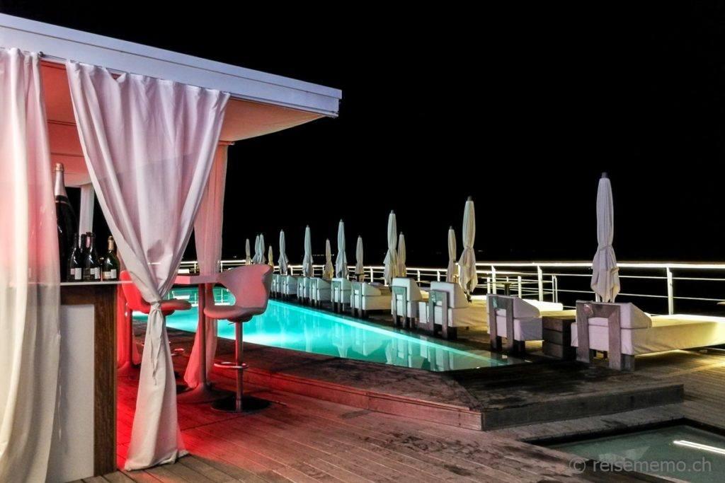 Eleganter Beach Club mit Pool nachts