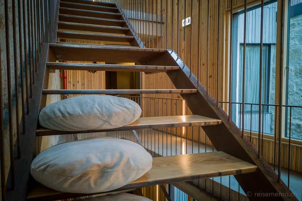 Lichthof und markante Treppe mit Sitzkissen
