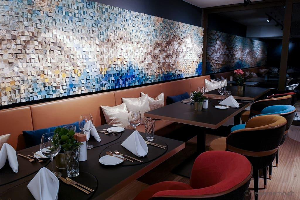 Holzrelief von Kasia Mc Art an der Wand des Hotelrestaurants Glacier