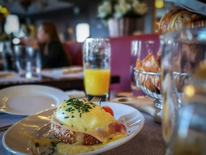 Egg Bénédict mit Brotkorb auf dem Brunch-Tisch