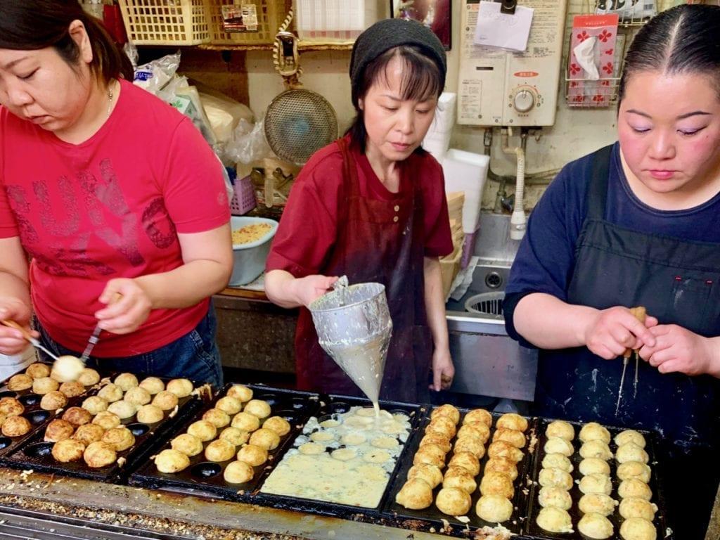 Drei Frauen bereiten Takoyaki zu