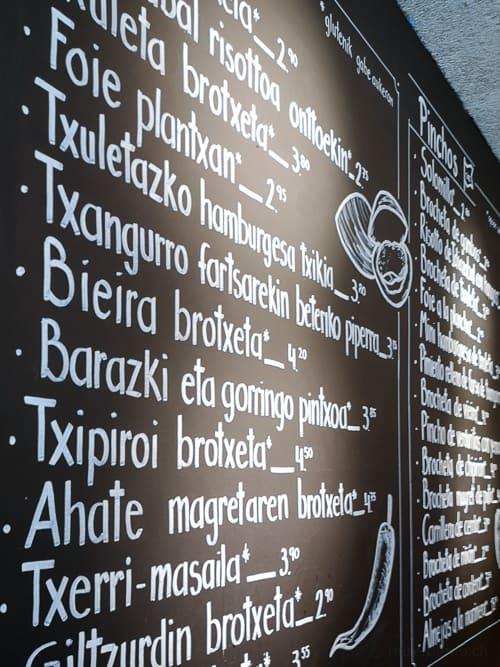 Speisekarte mit baskischen Pintxo-Namen, daneben auf Spanisch