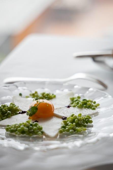 Glasteller mit jungen Erbsen und mariniertem Eigelb