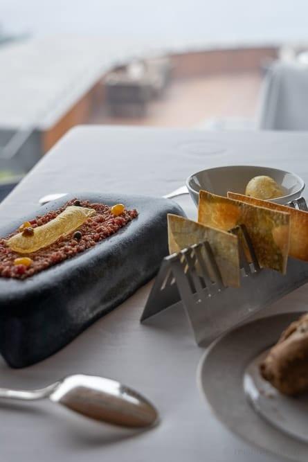 Schale mit Kartoffelsoufflé auf Rindstatar mit Kräuterbrot