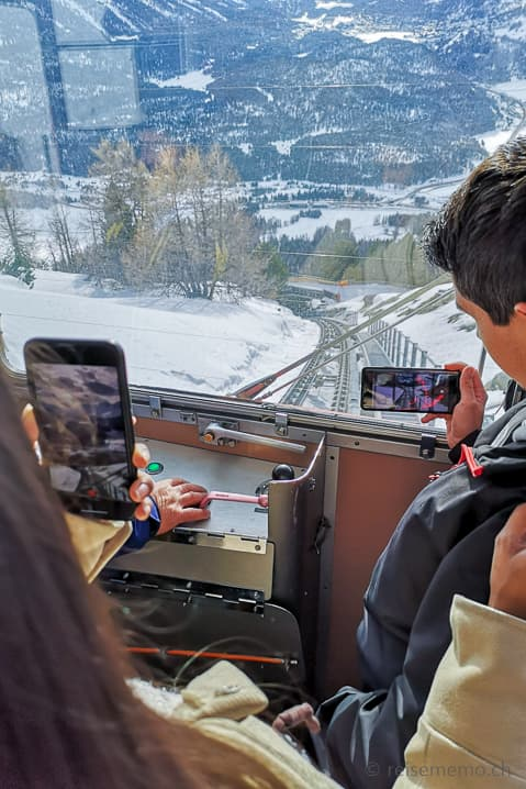 Touristen filmen die steile Abfahrt mit historischen Standseilbahn Muottas Muragl