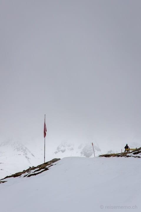 Wanderer geniesst die Aussicht vom Muottas Muragl auf die Engadiner Seenplatte