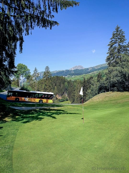 Postauto fährt durch den Golfplatz Vulpera