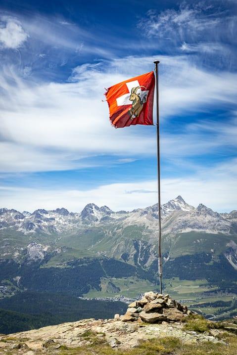 Schweizerfahne mit Bünder Steinbock vor dem Piz Ot