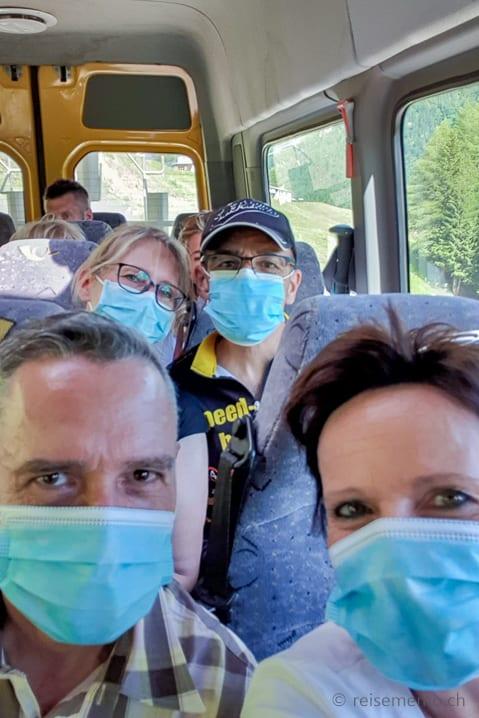 Wanderer mit Schutzmasken im Postauto