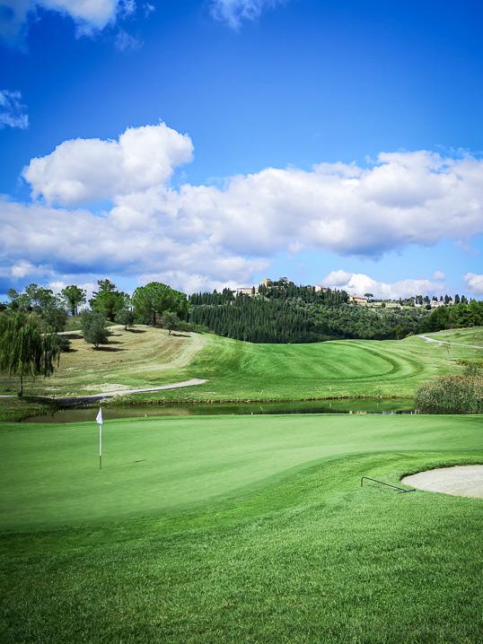 Green mit Golffahne und Dörfchen Castelfalfi auf dem Hügel