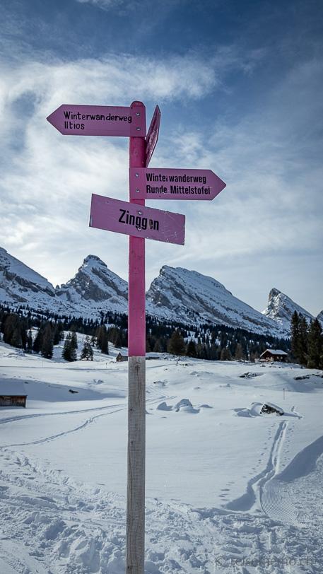 Pinkfarbener Winterwegweiser Zinggen der Sagenweg Winterwanderung