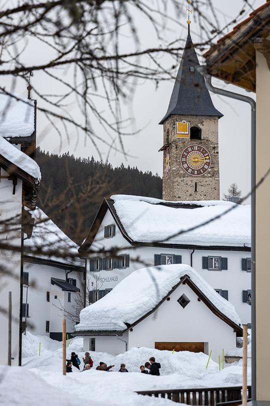 Kirche und Schulhaus im winterlichen Dorfkern von Parpan