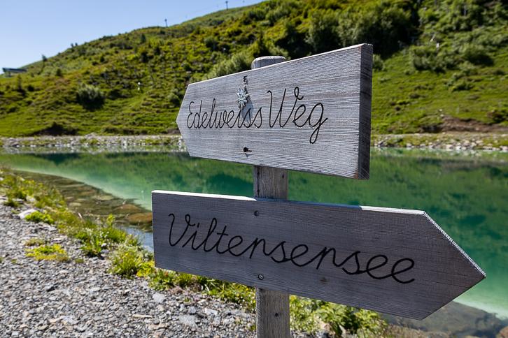 Schneekanonenwasserreservoir mit Wegweisern Edelweiss Weg und Viltersersee