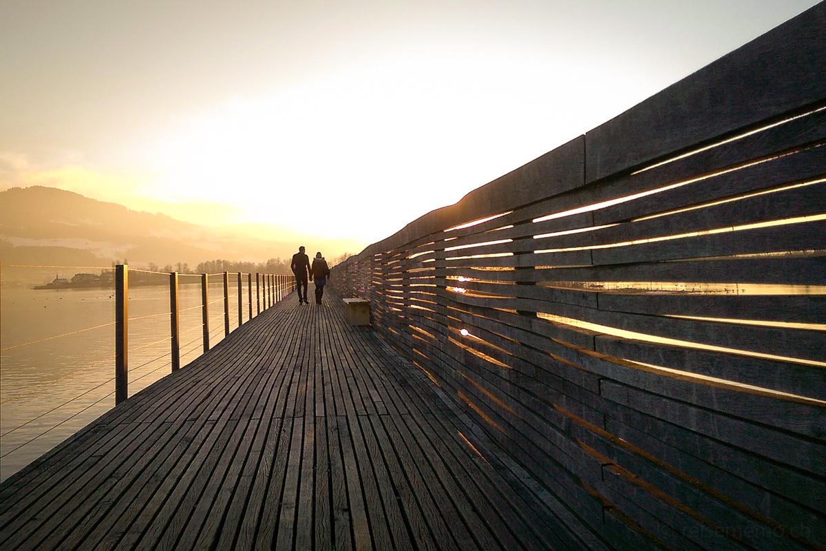Paar im Sonnenuntergang auf dem Holzsteg bei Rapperswil