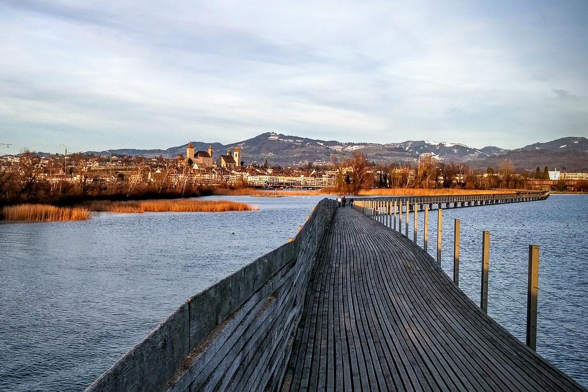 Holzbrücke mit Sicht auf das Schloss Rapperswil und den Bachtel